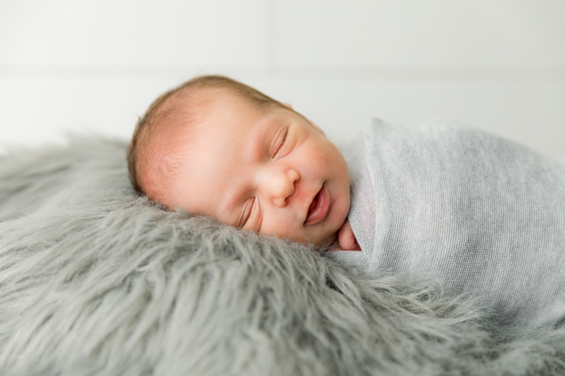 Smiling Newborn during his queen creek newborn photography session.