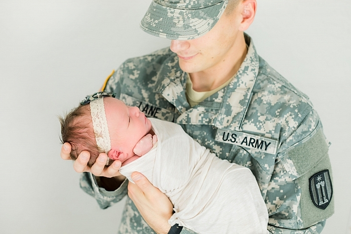 military dad holding newborn baby